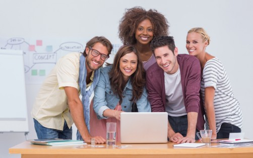 Creative team standing at desk with laptop and smiling at camera