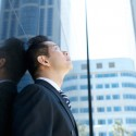 Businessman looking up at buildings