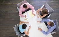 Four businesspeople at boardroom table
