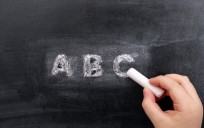 Childs hand writing ABC on blackboard