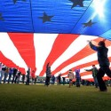 Photo of large flag unfurled across the Grainger Stadium infield during the National Anthem prior to opening game
