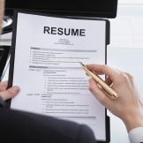 Businessman Analyzing Resume At Office Desk