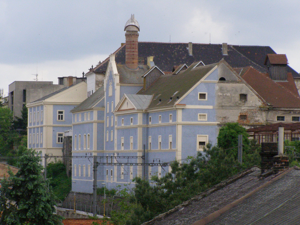 Castle in Kolín with new facade and crumbling building behind.
