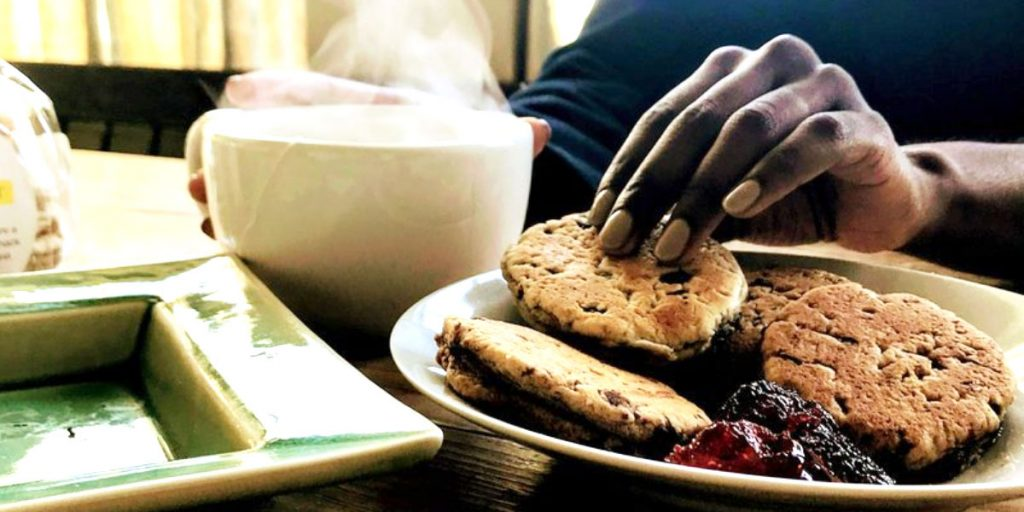 photo of a person picking up a welsh cake and drinking a hot beverage