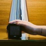 A hand reaching for an alarm clock.